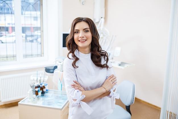 Стоматолог на рабочем месте. веселый доктор сидит в просторном современном офисе с доброй улыбкой