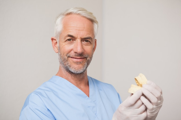 Dentist in blue scrubs holding mouth model