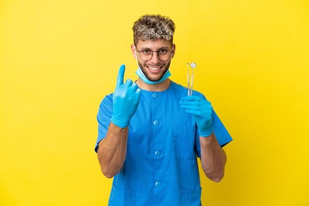 来るジェスチャーをしている黄色の背景に分離されたツールを保持している歯科医の白人男性