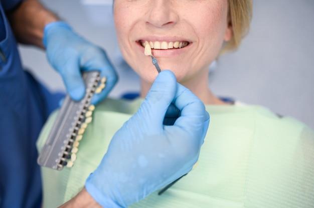 歯科医は歯科医院で歯科医の色で患者の歯のホワイトニングのレベルをチェックします