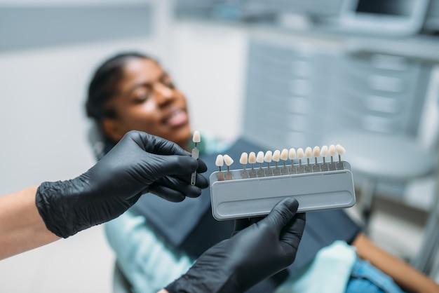 Dentist choosing the shade of teeth, dental clinic