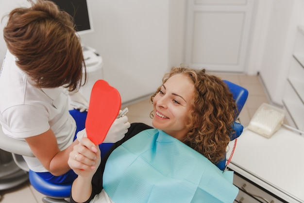 The dentist comparing patient's teeth shade with samples for bleaching treatment