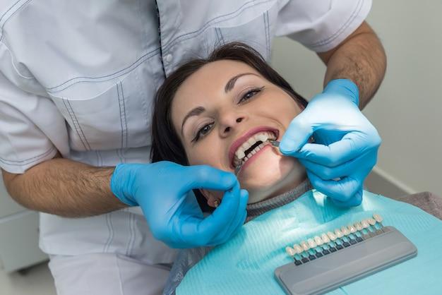 환자 치아를 크라운 샘플러와 비교하는 치과 의사