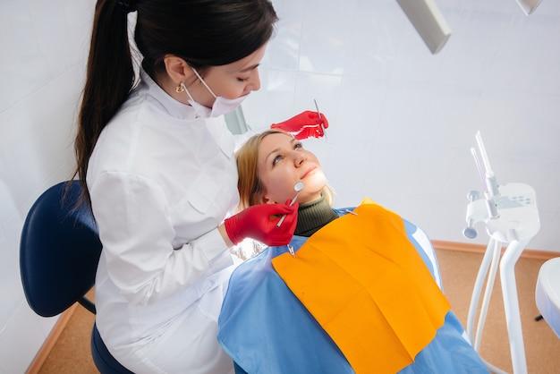 Стоматолог проводит обследование и консультацию пациента. лечение зубов