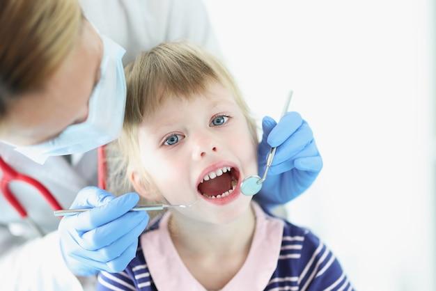 Стоматолог проводит медицинское обследование зубов маленькой девочки