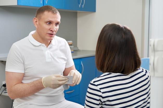 Стоматолог консультирует пациента, сидящего в кресле в своем офисе
