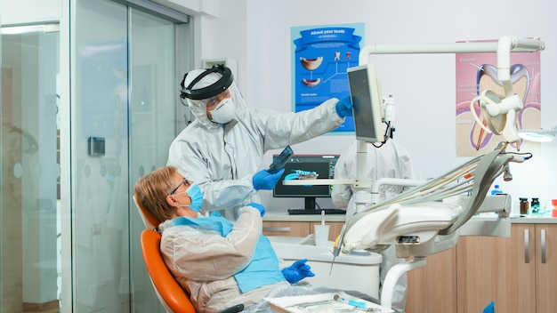 Dentist in coverall showing patient situation of teeth x-ray image during global pandemic. assistant and doctor talking with senior woman wearing protection suit, face shield, mask and gloves.