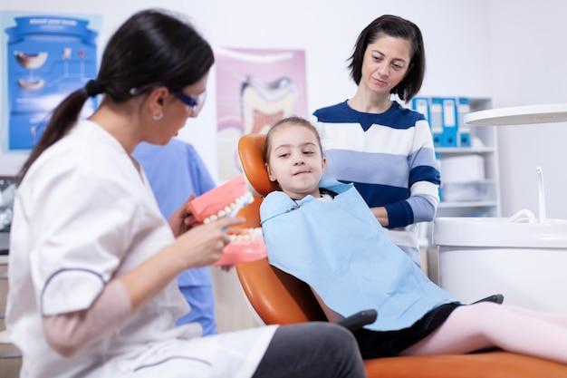 Стоматолог демонстрирует гигиену полости рта маленькому ребенку в нагруднике и родителю. маленькая девочка и мать, слушая стоматолога, говорят о гигиене зубов в стоматологической клинике, держа модель челюсти.
