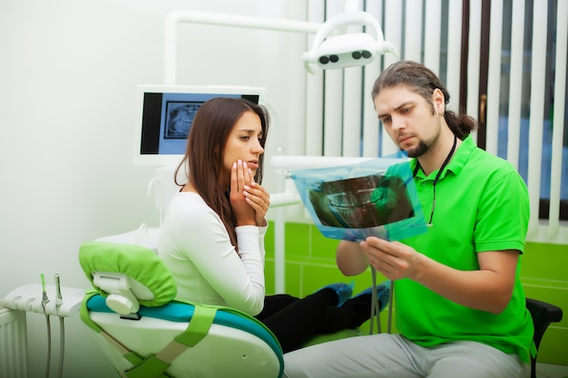 Dentist in dental office talking with female patient and preparing for treatment