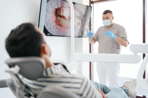 Стоматолог обсуждает с лежащим пациентом, показывая изображение его зубов на экране
