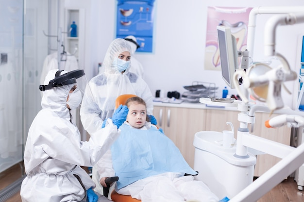 Dentist doctor in the course little kid consultation in dentistery office. stomatolog in protectie suit for coroanvirus as safety precaution holding child teeth x-ray during consultation.