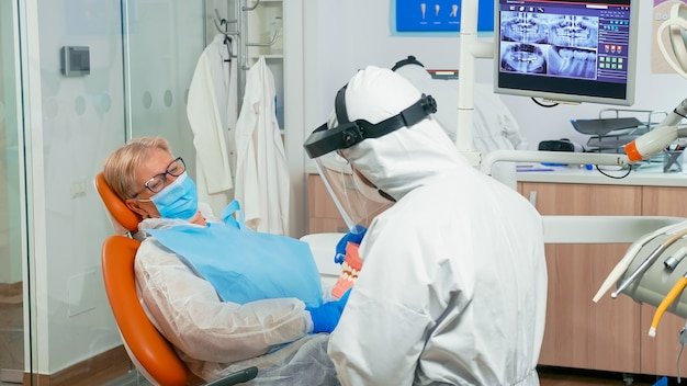 Dentist doctor in coverall showing the correct dental hygiene using mock-up of skeleton of teeth during coronavirus pandemic. medical team wearing protection suit, face shield mask and gloves.
