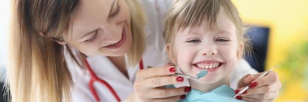 Врач стоматолог исследует зубы концепции услуг детского стоматолога маленькой девочки