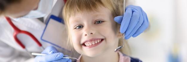 Врач стоматолог исследует зубы улыбающейся девочки в клинике