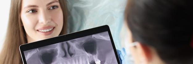 歯科医が女性患者の顎のレントゲン写真を検査します
