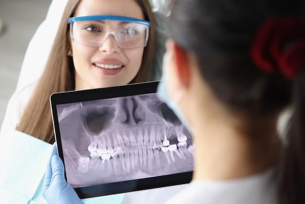 歯科医は椅子のタブレット画面でx線写真を調べる女性患者です