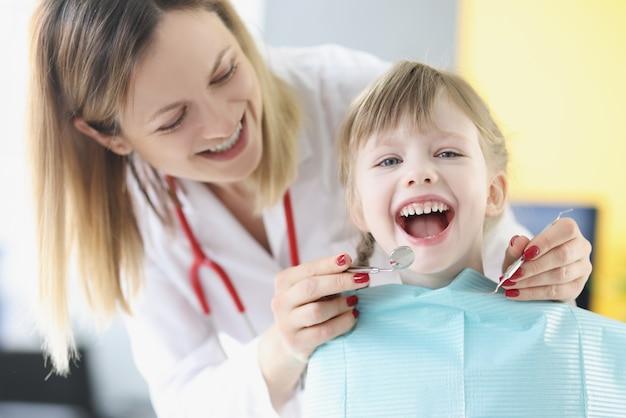 Врач стоматолог исследует зубы маленькой девочки с помощью инструментов в клинике стоматологической помощи для