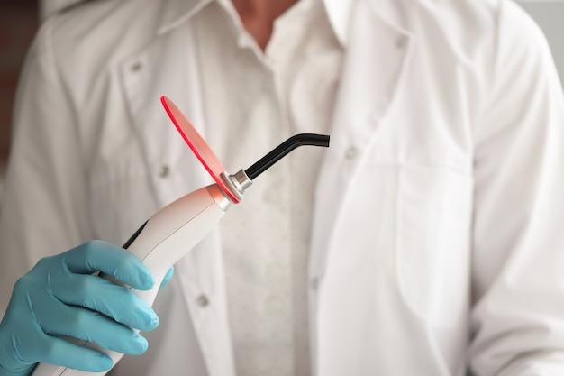 Врач-стоматолог держит в руке лампу для пломбирования зуба