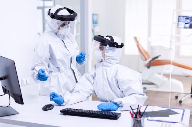 口腔病学クリニックで看護師と話し合っているppeスーツの歯科医。安全対策として、歯科受付でコロナウイルスのパンデミックに対する保護具を着用している医療チーム。