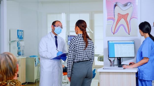 치과 의사는 여자를 심문하고 대기 구역에 서 있는 클립보드에 메모를 합니다. 클리닉의 붐비는 리셉션에서 말하는 구강 전문의에게 치과 문제를 설명하는 젊은 환자.