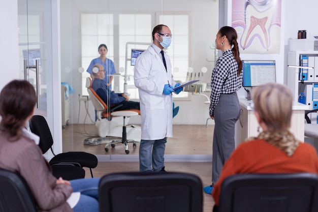 Dentist doctor interrogating woman and taking notes on clipboard standing in waiting area