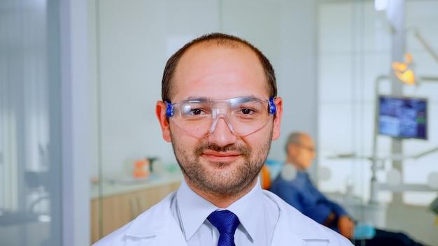 치과 의사는 노인 환자가 치과 위생을 위해 백그라운드에서 그를 기다리는 동안 카메라를 보고 웃고 있습니다. 구강 클리닉에서 웹캠 앞에 서 있는 보호 안경을 쓴 구강 전문의.