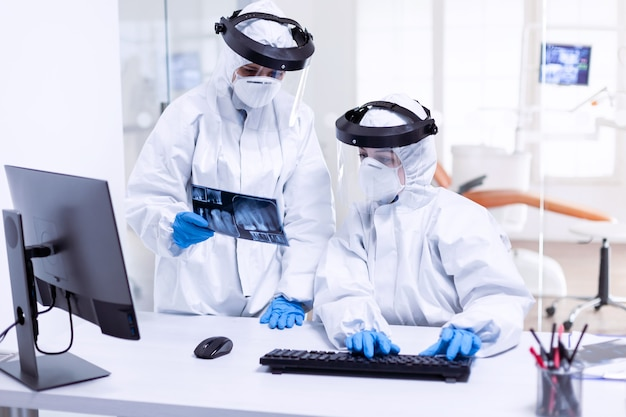 Dentist doctor and nurse in ppe suit against covid-19 and nurse holding teeth x-ray. medical specialist wearing protective gear against coronavirus during global outbreak looking at radiography in den