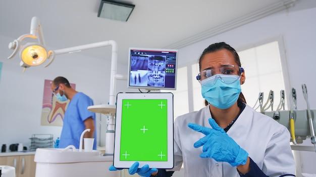 歯科医が緑色の画面でタブレットを見せ、歯科x線撮影と歯の感染症の診断について説明します。モックアップ、コピースペース、クロマディスプレイを指すフェイスマスクを持つ口腔病学のスペシャリスト