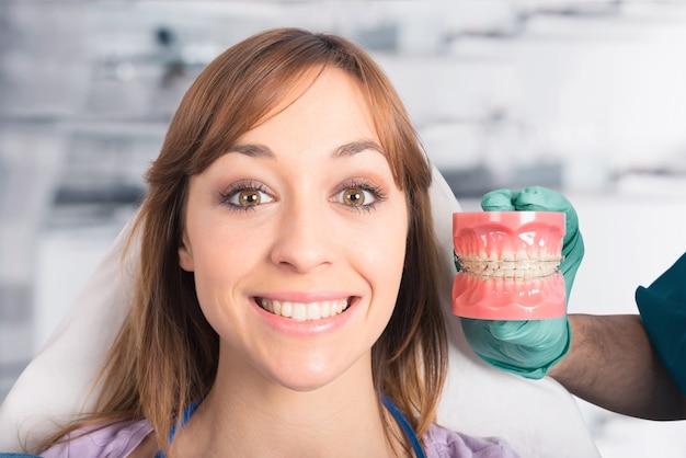 치과 의사가 보조기를 적용하는 방법을 보여줍니다.
