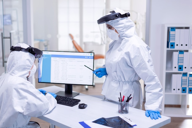 Ppe 양복을 입은 치과 의사가 리셉션에서 환자 일정에 대해 간호사와 이야기하고 있습니다. 안전 예방책으로 치과 진료실에서 코로나바이러스 전염병에 대한 보호 장비를 착용한 의학 팀.