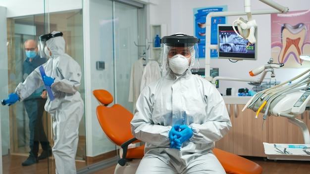코로나바이러스 동안 카메라를 보고 있는 작업복을 입은 치과 의사. 전염병 기간 동안 보호복, 안면 보호대, 마스크, 보조자가 있는 장갑을 착용한 화상 통화 교정