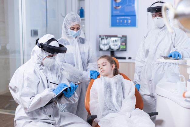 Dentist doctor with face mask and coverall holding clipboard dressed in coverall stomatologist during covid19 wearing ppe suit doing teeth procedure of child sitting on chair.