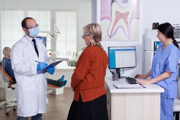 口腔病学待機エリアの廊下で年配の女性患者に診断を説明するフェイスマスクを持った歯科医。歯の治療のために椅子に座っている老人。