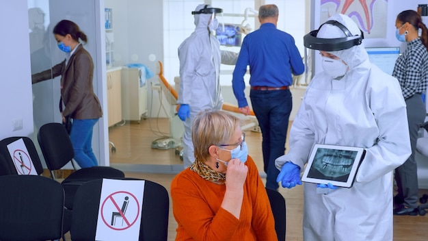태블릿 디스플레이를 가리키는 안면 보호대를 가진 치과 의사는 전 세계적으로 유행하는 동안 노인 환자에게 치과 엑스레이를 설명합니다. 보호복을 입은 간호사, 전체, 마스크와 장갑, 뉴 노멀
