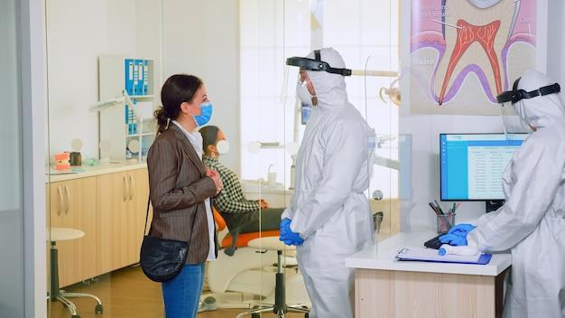 대기실에서 환자에게 치아 치료를 전반적으로 설명하는 치과 의사, 세계적 유행병 동안 수술 단계를 계획합니다. 코로나바이러스 발생 시 새로운 일반 치과 방문의 개념.