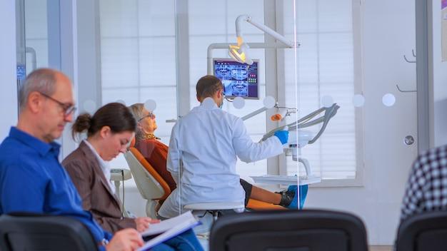 混雑した専門の歯科医院でシニア患者と一緒に働く歯科医。レセプションエリアで待っている人がフォームに記入している間、歯科矯正医が口腔病学の椅子に座っている女性に話しかける