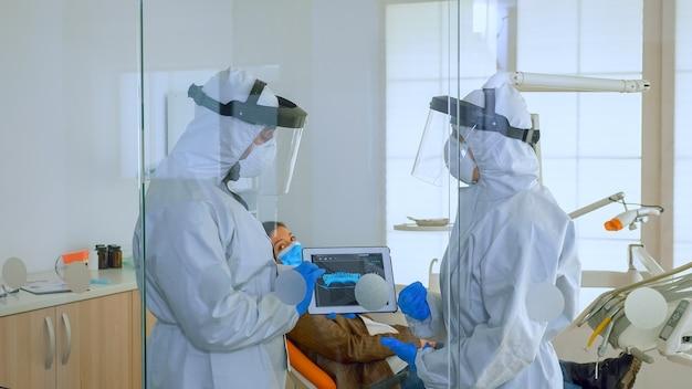 コロナウイルスの間に歯科医院で歯科用x線を説明するタブレットを全体的に使用している歯科医。フェイスシールドとマスクを身に着けている男性がデジタルデバイスを使用してx線撮影を看護することを示しています