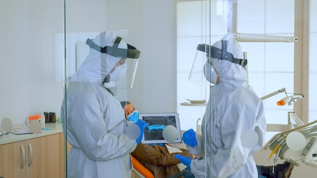 Dentist doctors in overall using tablet explaining dental x ray in stomatologic office during coronavirus. man wearing face shield and mask showing to nusrse radiography using digital device