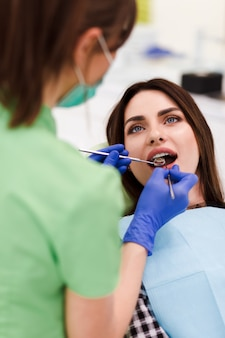 Dentist does an oral examination. pretty patient woman came to the dentist's appointment
