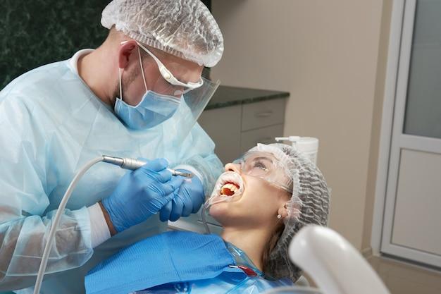女性患者に歯科治療をしている歯科医。現代の患者の歯を調べる歯科医