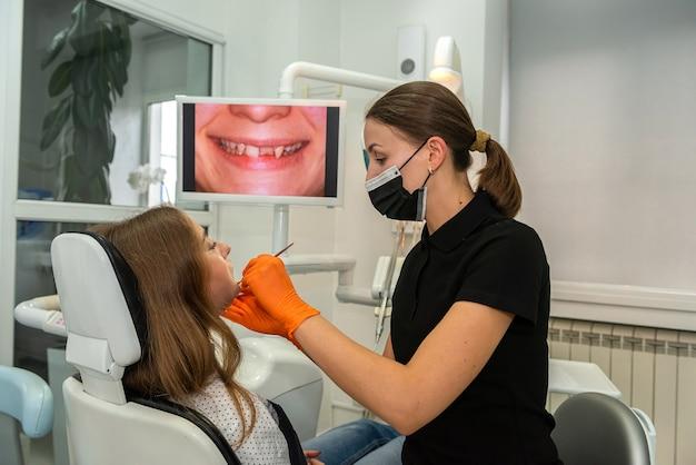 歯科医院で患者の手技をしている歯科医。ヘルスケアの概念