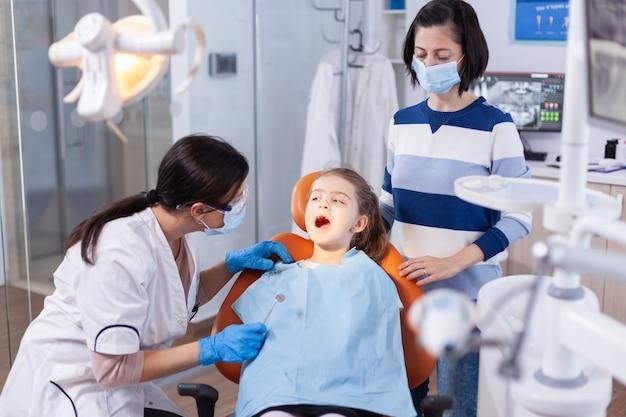よだれかけを着て歯科用椅子に座っている少女の歯のチェックをしている歯科医。現代の技術を使用した口腔病学オフィスでの虫歯相談中の歯科専門医。