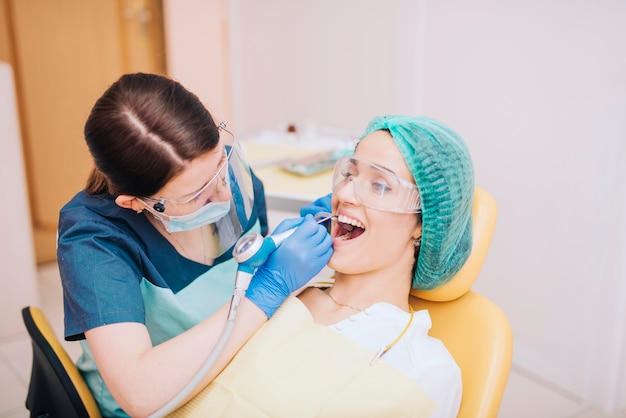 Dentist drilling teeth of female patient