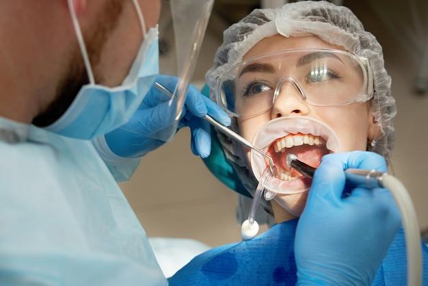女性患者に歯を掘削する歯科医