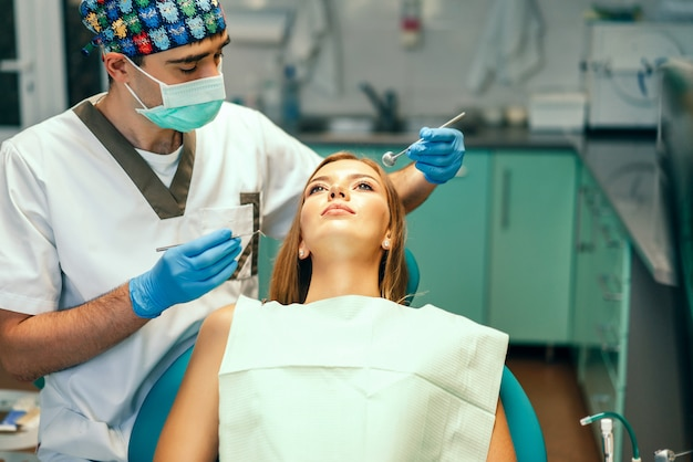 Dentist examine female patient with braces in denal office.