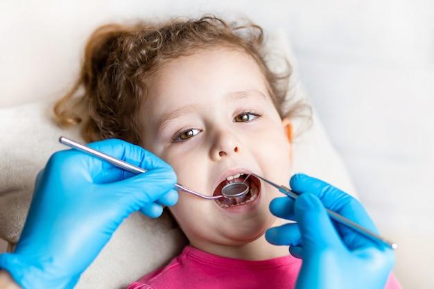 歯科医はツールで女の子の歯を調べます Premium写真