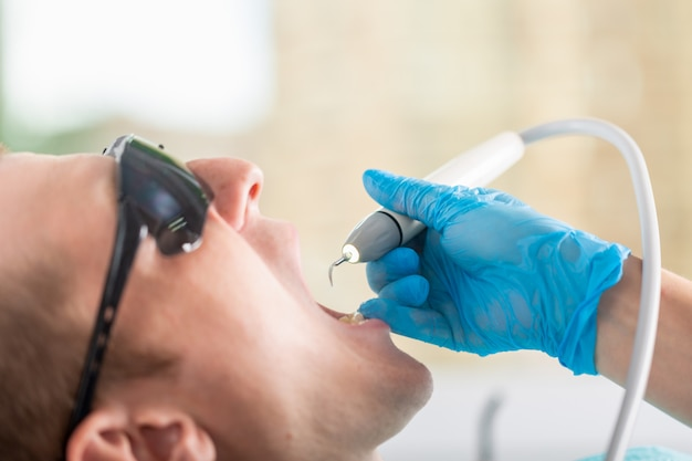 A dentist examines the oral cavity of the patient
