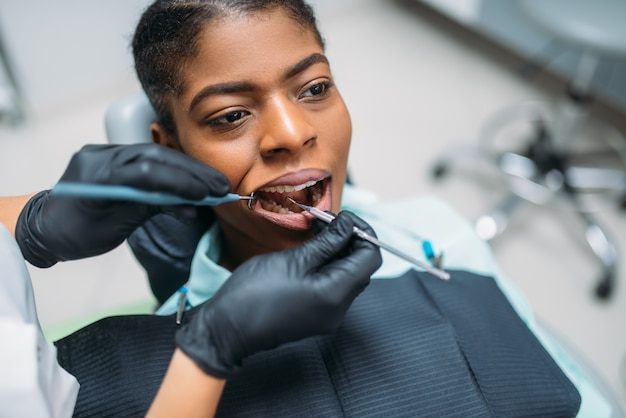 Dentist examines the teeth of female patient in dental clinic.