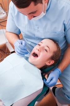 歯科医は10代の少女の患者の口を調べます