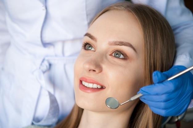 Стоматолог осматривает зубы пациента в стоматологической клинике.